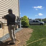 picture of employee spraying solutions on the side of home