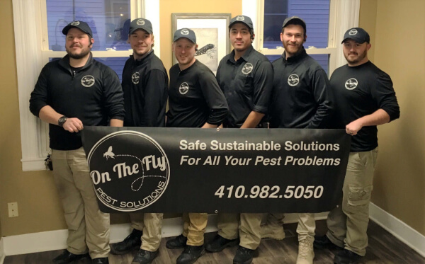 On The Fly Pest Solutions team of employees holding company banner